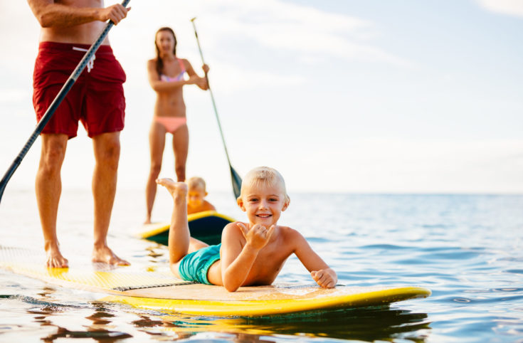 Family,Having,Fun,Stand,Up,Paddling,Together,In,The,Ocean