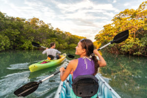 Girl in purple shirt and man in a gray shirt kayaking in Florida.